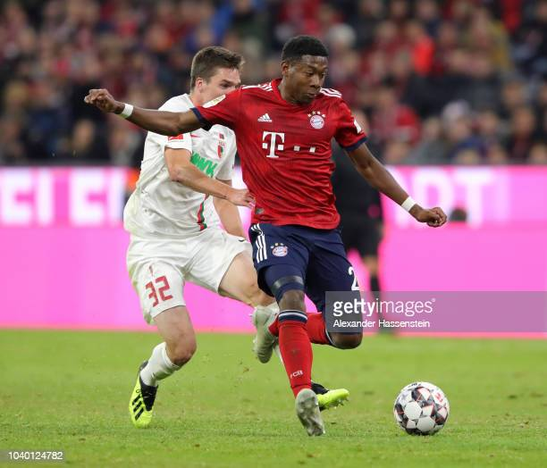 David Alaba of Bayern Munich is challanged by Raphael Framberger of Augsburg during the Bundesliga match between FC Bayern Muenchen and FC Augsburg...