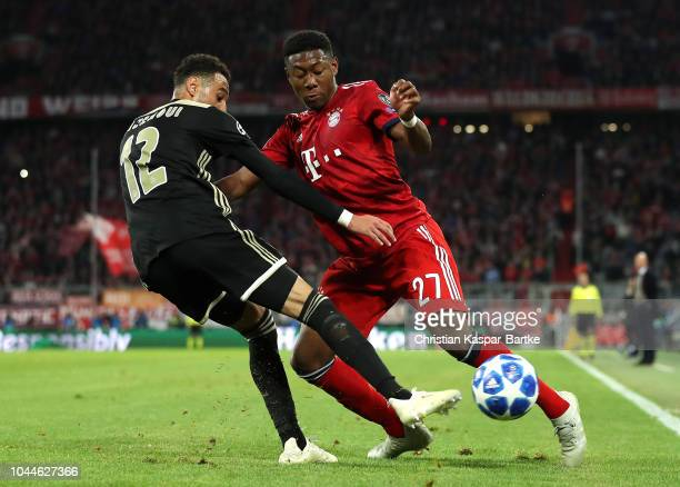 David Alaba of Bayern Munich is challenged by Noussair Mazraoui of Ajax during the Group E match of the UEFA Champions League between FC Bayern...