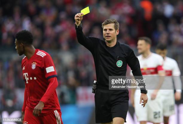 David Alaba of Bayern Munich is shown a yellow card by referee Frank Willenborg during the Bundesliga match between FC Bayern Muenchen and VfB...
