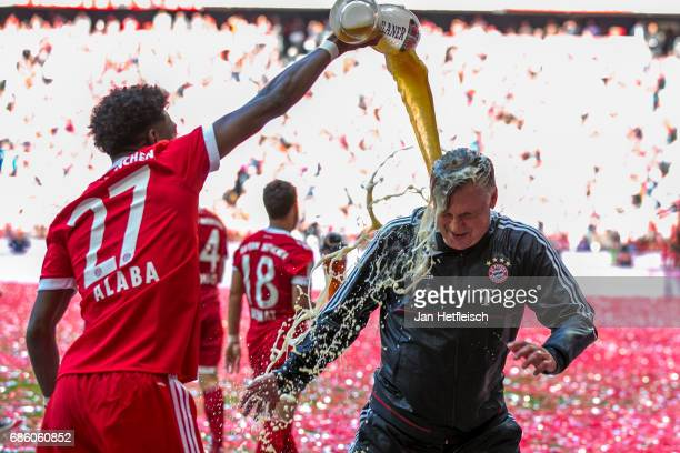 David Alaba of FC Bayern Muenchen and Carlo Ancelotti head coach of FC Bayern Muenchen celebrates with beer after the Bundesliga match between Bayern...