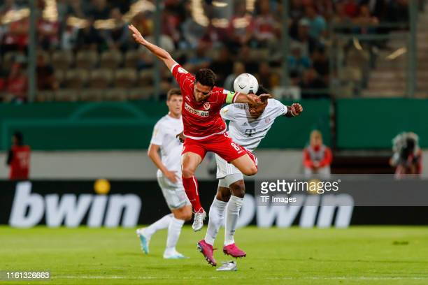 David Alaba of FC Bayern Muenchen and Dimitar Rangelov of Energie Cottbus battle for the ball during the DFB Cup first round match between Energie...
