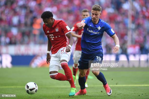David Alaba of FC Bayern Muenchen challenges Felix Platte of SV Darmstadt during the Bundesliga match between Bayern Muenchen and SV Darmstadt 98 at...