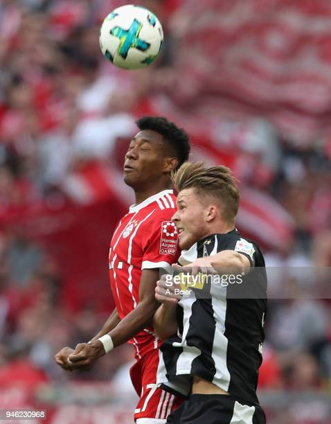 David Alaba of FC Bayern Muenchen heads for the ball with Nico Elvedi of Moechengladbach during the Bundesliga match between FC Bayern Muenchen and...