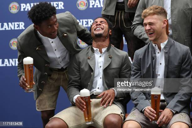 David Alaba of FC Bayern Muenchen jokes with his team mates Serge Gnabry and Joshua Kimmich during the FC Bayern Muenchen and Paulaner photo session...