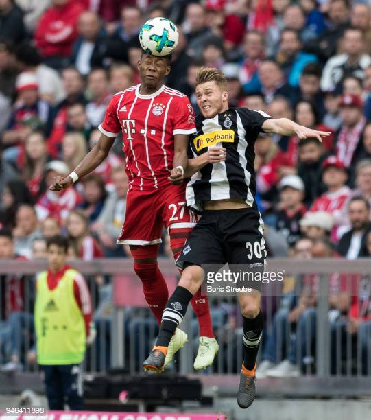 David Alaba of FC Bayern Muenchen jumps for a header with Nico Elvedi of Borussia Moenchengladbach during the Bundesliga match between FC Bayern...
