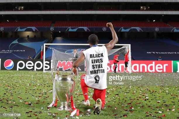 David Alaba of FC Bayern Muenchen kneels down in support of the Black Live Matter movement next to the UEFA Champions League Trophy following his...