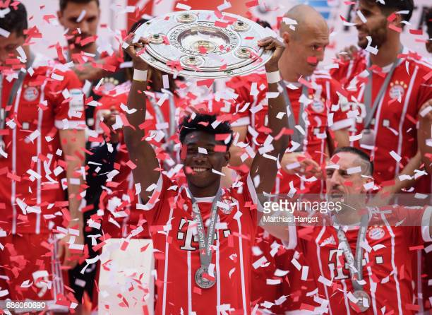 David Alaba of FC Bayern Muenchen lifts the Championship trophy in celebration of the 67th German Championship title following the Bundesliga match...