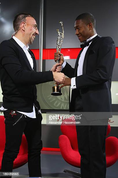 David Alaba of FC Bayern Muenchen receives his Austria's Sportsmen of the Year 2013 award from his team mate Franck Ribery at Bayern Muenchen's...