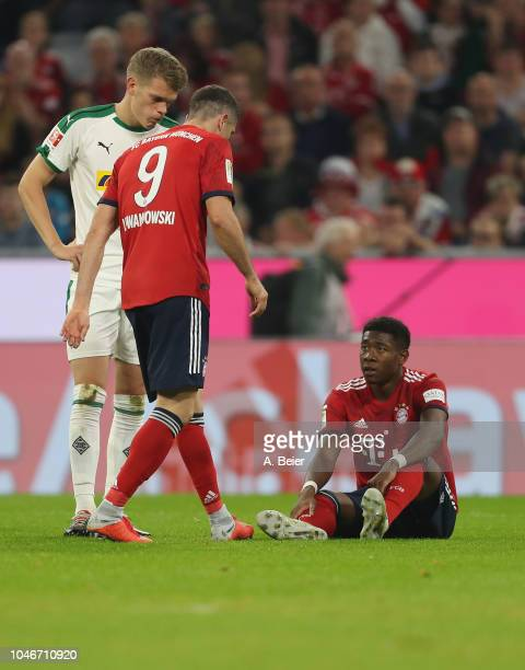 David Alaba of FC Bayern Muenchen sits on the pitch injured during the Bundesliga match between FC Bayern Muenchen and Borussia Moenchengladbach at...