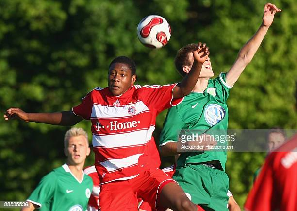 David Alaba of Muenchen battles for the ball with Robin Knoche of Wolfsburg during the first match of the DFBJuniorenVereinspokal semi final at the...