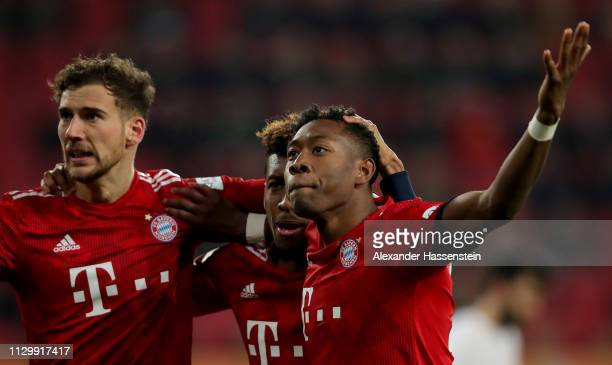 David Alaba of Muenchen celebrate with team mate Kingsley Coman and Leon Goretzka after he scores the 3rd goal during the Bundesliga match between FC...