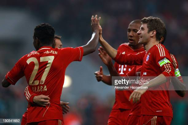 David Alaba of Muenchen celebrates scoring the second team goal with his team mates Thomas Mueller during the DFB Cup second round match between FC...