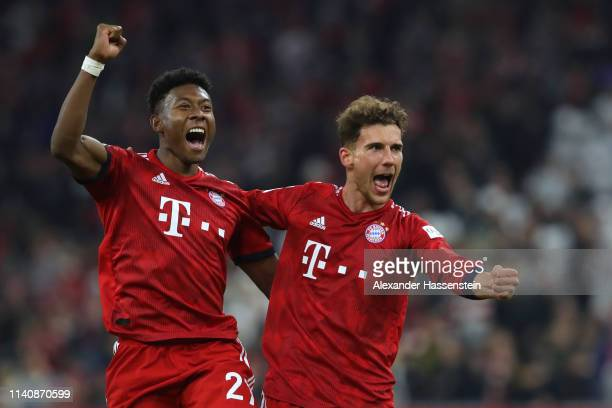 David Alaba of Muenchen celebrates with his team mate Leon Goretzka after winning the Bundesliga match between FC Bayern Muenchen and Borussia...