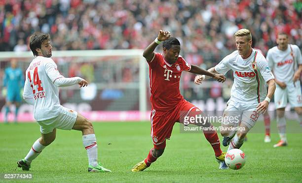 David Alaba of Muenchen is challenged by Andre Hahn and Jan Moravek of Augsburg during the Bundesliga match between FC Bayern Muenchen and FC...