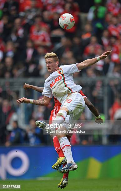 David Alaba of Muenchen is challenged by Andre Hahn of Augsburg during the Bundesliga match between FC Bayern Muenchen and FC Augsburg at Allianz...