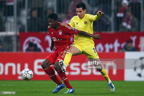 David Alaba of Muenchen is challenged by Hernan Perez of Villarreal during the UEFA Champions League Group A match between FC Bayern Muenchen and...