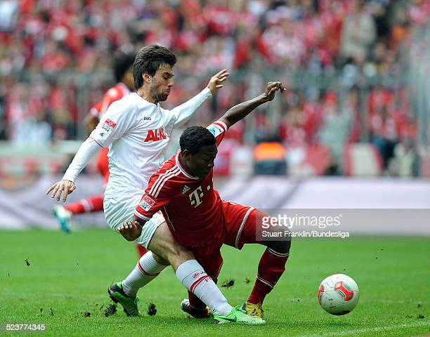 David Alaba of Muenchen is challenged by Jan Moravek of Augsburg during the Bundesliga match between FC Bayern Muenchen and FC Augsburg at Allianz...