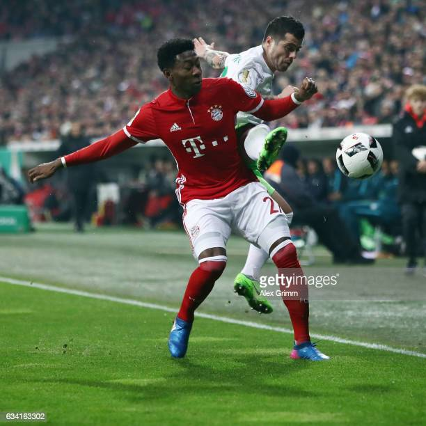 David Alaba of Muenchen is challenged by Vieirinha of Wolfsburg during the DFB Cup Round Of 16 match between Bayern Muenchen and VfL Wolfsburg at...