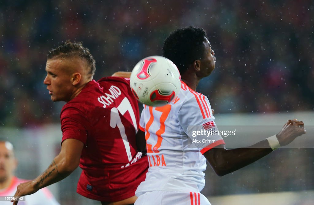 David Alaba (R) of Muenchen jumps for a header with Jonathan Schmid of Freiburg during the Bundesliga match between SC Freiburg and FC Bayern Muenchen at MAGE SOLAR Stadium on November 28, 2012 in Freiburg im Breisgau, Germany.