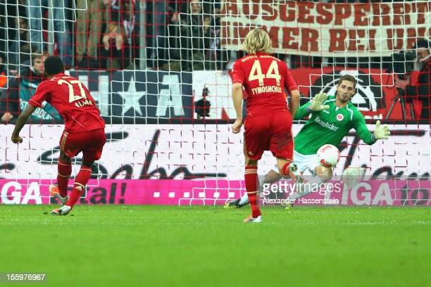 David Alaba of Muenchen scores the 2nd team goal with a penalty kick against Kevin Trapp keeper of Frankfurt during the Bundesliga match between FC...