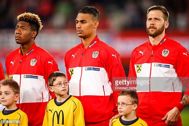 David Alaba Rubin Okotie and Guido Burgstaller of Austria line up during the national anthem prior to the international friendly match between...