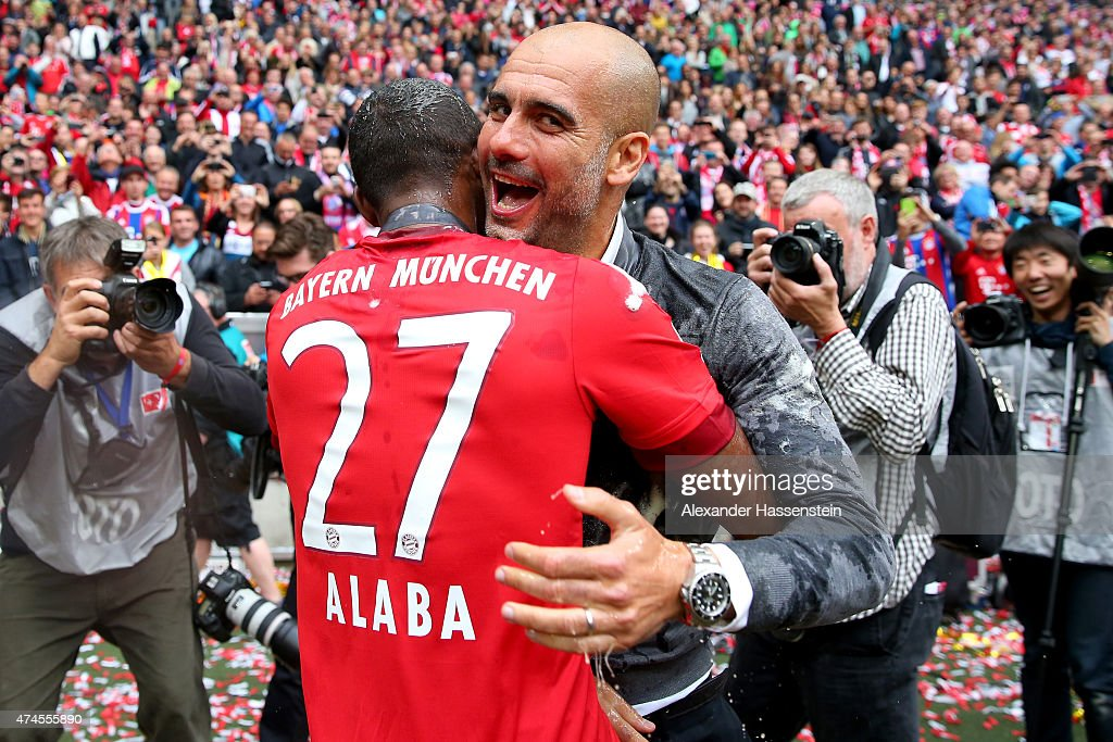 David Alaba (L) smile with head coach Josep Guardiola of Bayern Muenchen after a fight with a beer mug to celebrate the German Championship after the Bundesliga match FC Bayern Muenchen and 1. FSV Mainz 05 at Allianz Arena on May 23, 2015 in Munich, Germany.