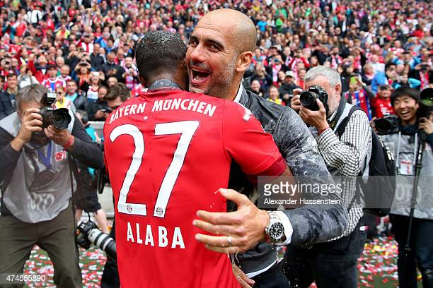 David Alaba smile with head coach Josep Guardiola of Bayern Muenchen after a fight with a beer mug to celebrate the German Championship after the...