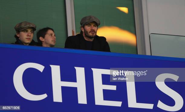 David and Brooklyn Beckham look on from the stands prior to The Emirates FA Cup QuarterFinal match between Chelsea and Manchester United at Stamford...