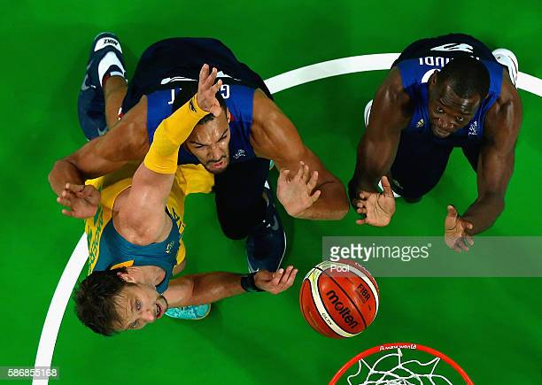 David Andersen of Australia defends Rudy Gobert of France as Charles Kahudi looks on in the Men's Preliminary Round Group A match on Day 1 of the Rio...