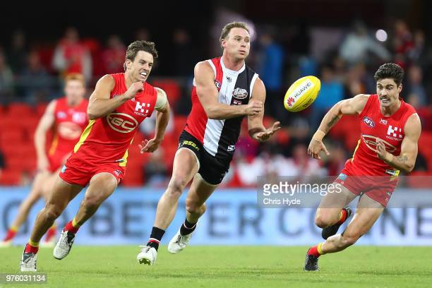 David Armitage of the Saints handballs during the round 13 AFL match between the Gold Coast Suns and the St Kilda Saints at Metricon Stadium on June...