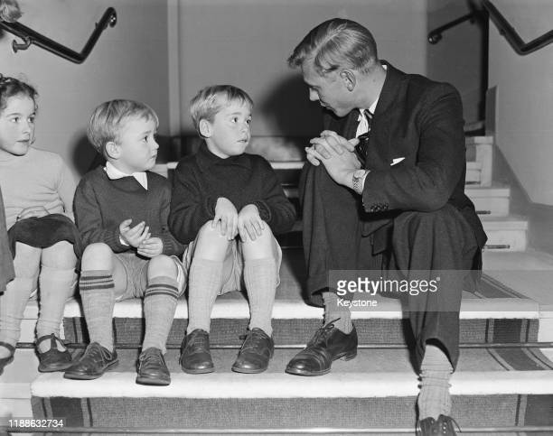 David Attenborough talking to three members of his audience before the start of one of his Royal Geographical Society Christmas Lectures For Children...