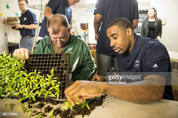 David Avey shows Reggie Williams of the Tulsa 66ers how to repot plants during the NBA DLeague community relations event at A New Leaf a nonprofit...
