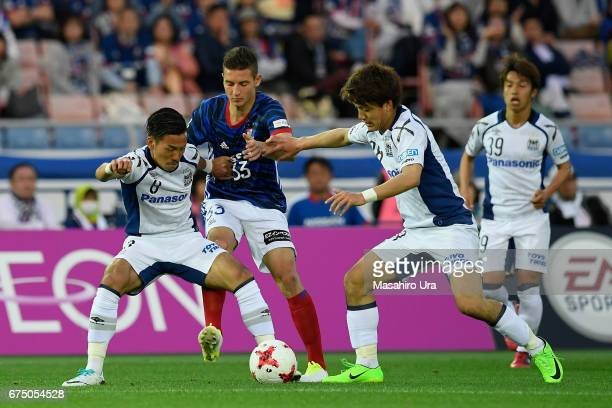 David Babunski of Yokohama FMarinos competes for the ball against Yosuke Ideguchi and Ritsu Doan of Gamba Osaka during the JLeague J1 match between...