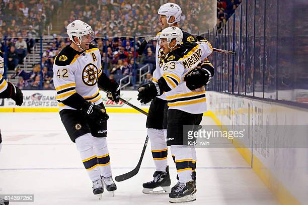 David Backes and Zdeno Chara congratulate Brad Marchand after he scored a goal during the third period of the game against the Columbus Blue Jackets...