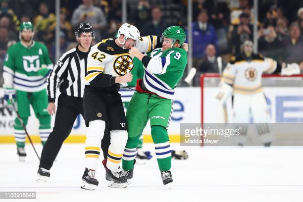 David Backes of the Boston Bruins and Micheal Ferland of the Carolina Hurricanes fight during the first period at TD Garden on March 05 2019 in...