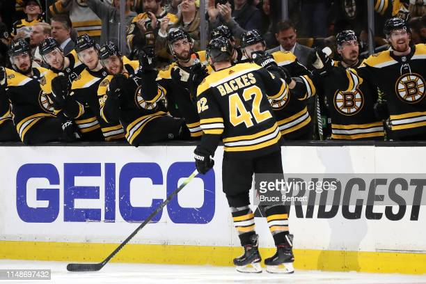 David Backes of the Boston Bruins celebrates with teammates after scoring a third period goal against Petr Mrazek of the Carolina Hurricanes in Game...