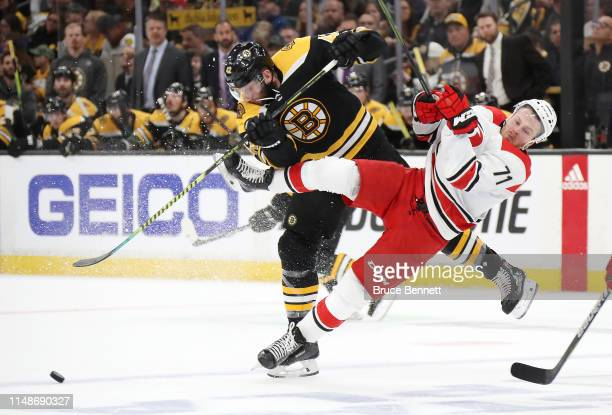 David Backes of the Boston Bruins checks Lucas Wallmark of the Carolina Hurricanes during the first period in Game Two of the Eastern Conference...