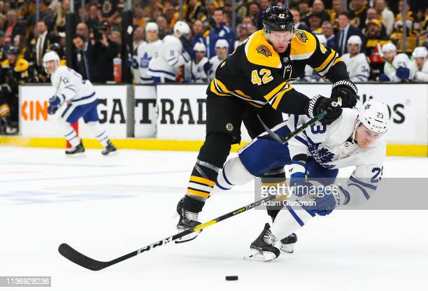 David Backes of the Boston Bruins checks Travis Dermott of the Toronto Maple Leafs in Game Two of the Eastern Conference First Round during the 2019...