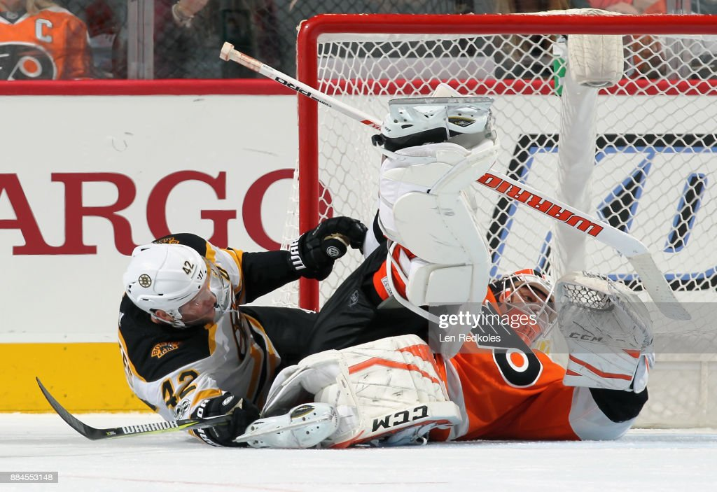 David Backes #42 of the Boston Bruins collides with goaltender Brian Elliott #37 of the Philadelphia Flyers on December 2, 2017 at the Wells Fargo Center in Philadelphia, Pennsylvania. The Bruins went on to defeat the Flyers 3-0.
