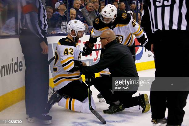David Backes of the Boston Bruins is checked on by head althetic trainer Don DelNegro and David Krejci after being elbowed by Dean Kukan of the...