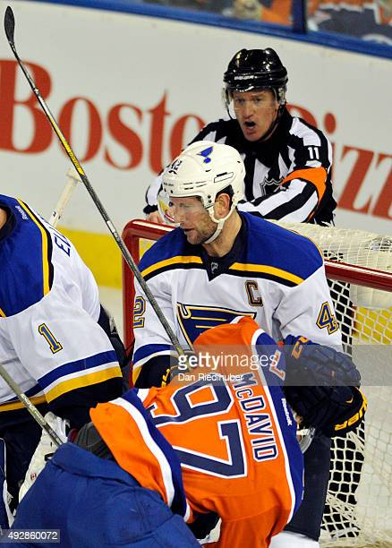 David Backes of the St Louis Blues collars Connor McDavid of the Edmonton Oilers as referee Kelly Sutherland a warning at Rexall Place on October 15...