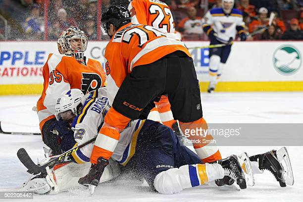 David Backes of the St Louis Blues collides with goalie Steve Mason of the Philadelphia Flyers in the first period at Wells Fargo Center on December...