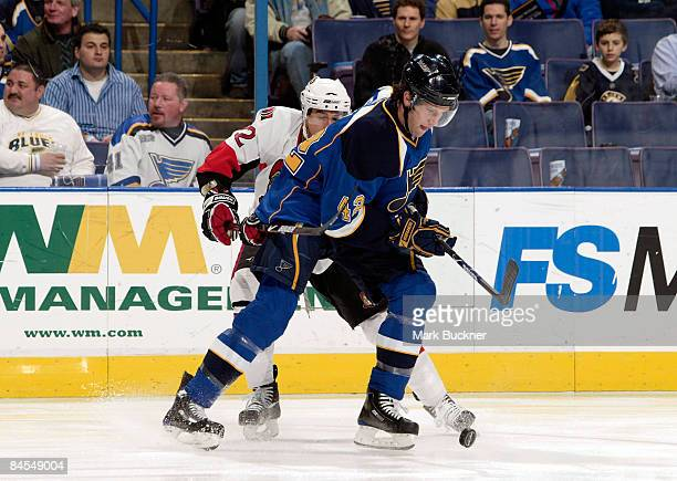 David Backes of the St Louis Blues handles the puck in front of Chris Kelly of the Ottawa Senators on January 29 2009 at Scottrade Center in St Louis...