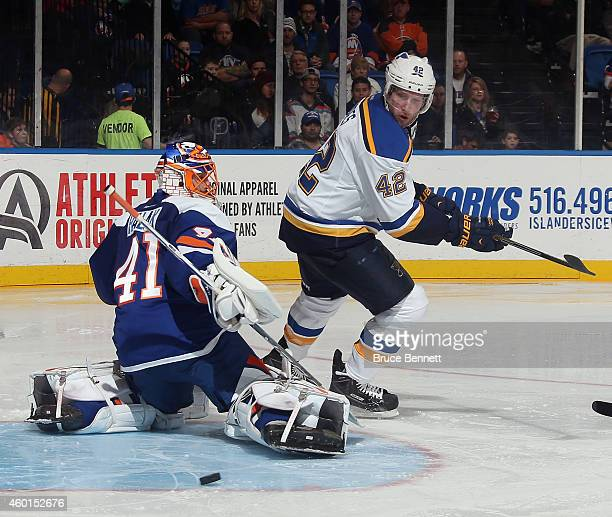 David Backes of the St Louis Blues skates against Jaroslav Halak of the New York Islanders at the Nassau Veterans Memorial Coliseum on December 6...