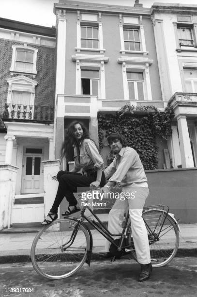 David Bailey and Marie Helvin on a bicycle in front of their London home August 18th 1977