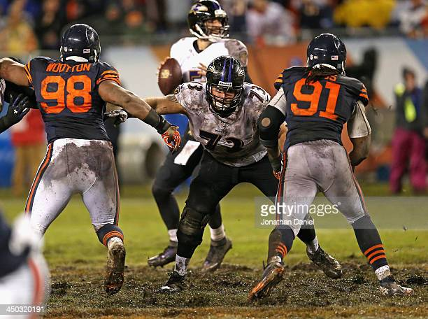David Bass and Corey Wootton#98 of the Chicago Bears rush against Marshal Yanda of the Baltimore Ravens at Soldier Field on November 17 2013 in...