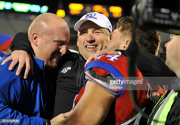 David Beaty head coach of the Kansas Jayhawks celebrates with a fan and fullback Michael Zunica after they beat the Texas Longhorns 2421 in the...