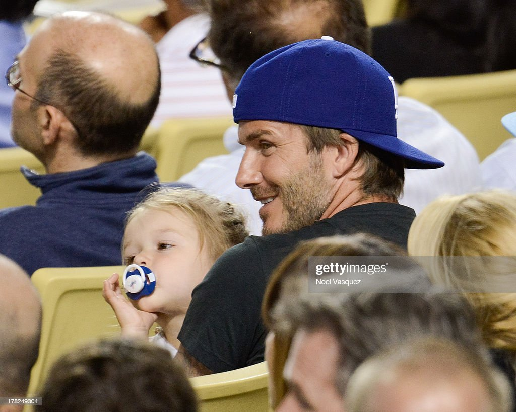 David Beckham (R) and daughter Harper Beckham attend a baseball game between the Chicago Cubs and the Los Angeles Dodgers at Dodger Stadium on August 27, 2013 in Los Angeles, California.