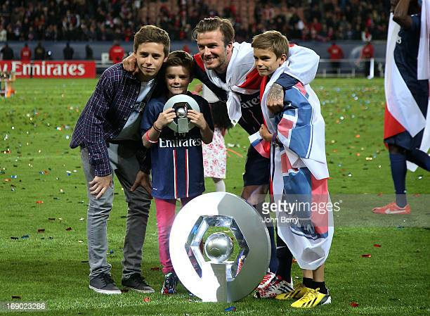 David Beckham and his sons Brooklyn Beckham Cruz Beckham and Romeo Beckham pose on the field during the celebration of PSG's french championship...
