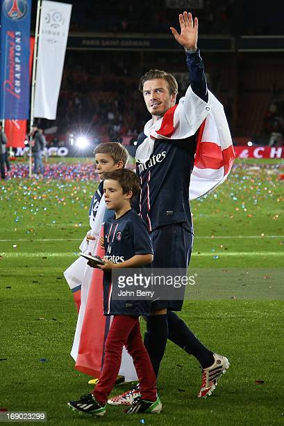 David Beckham and his sons Brooklyn Beckham, Cruz Beckham and Romeo Beckham walk on the field during the celebration of PSG's french championship...
